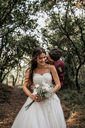 Groom kissing smiling bride in forest - DAPF00915