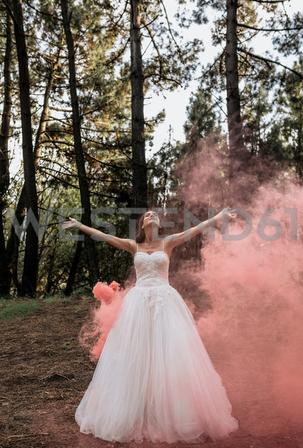 Woman wearing wedding dress in forest surrounded by clouds of smoke - DAPF00921
