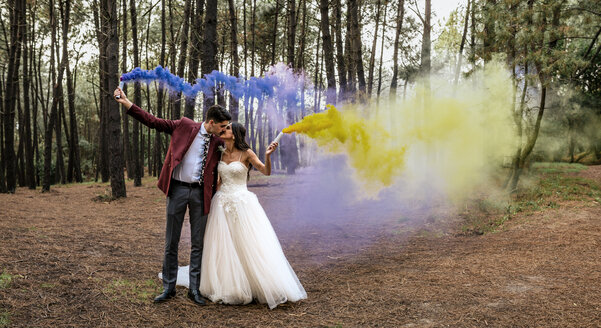 Bride and groom kissing in forest holding smoke torches - DAPF00924