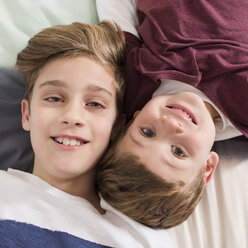 Top view of two smiling brothers lying on bed - SKCF00336