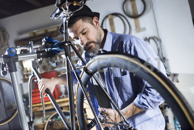 Man working on bicycle in workshop - JSRF00022