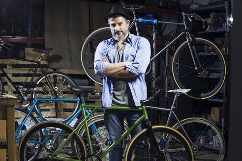 Portrait of confident man in bicycle workshop - JSRF00025