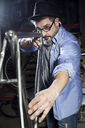 Man working on bicycle in workshop - JSRF00031