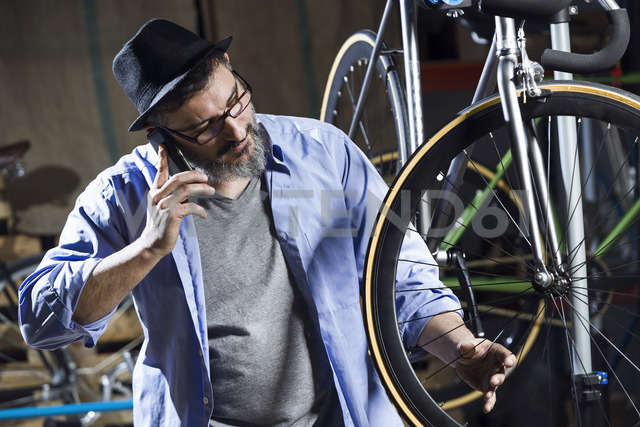 Man working on bicycle in workshop while talking on cell phone - JSRF00034