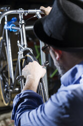 Man working on bicycle in workshop - JSRF00037