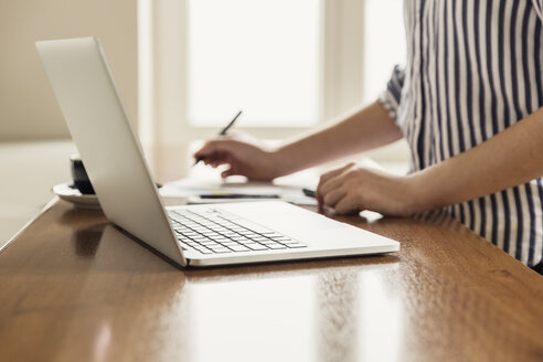 Close-up of woman with laptop and documents on table at home - JHAF00022