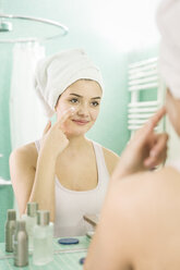 Young woman applying facial moisturizer at mirror in bathroom - JHAF00031