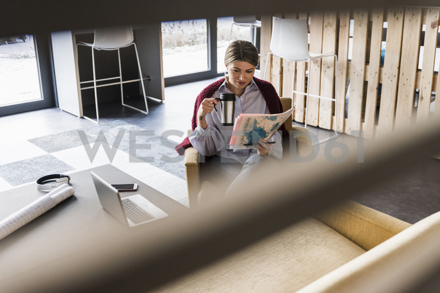 Young woman sitting in armchair reading documents - UUF12822