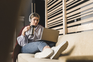 Young woman on couch with coffee and laptop - UUF12825