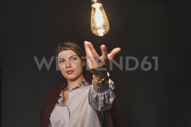 Young woman reaching for illuminated light bulb - UUF12828