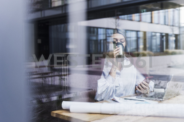 Young woman with laptop, cell phone and documents drinking coffee behind windowpane - UUF12834