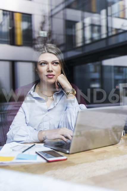 Young woman with laptop and documents behind windowpane - UUF12837