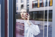 Young woman on cell phone behind windowpane - UUF12840