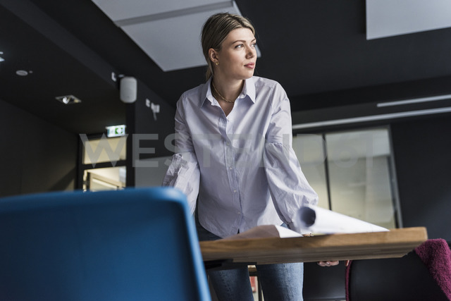 Young woman standing at table in office thinking - UUF12843