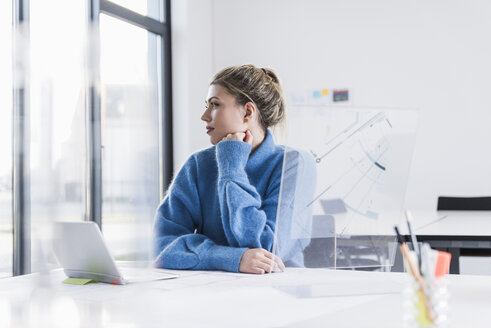 Young woman with laptop and transparent design at desk in office thinking - UUF12849
