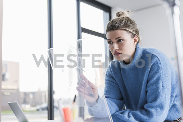 Young woman working on transparent design in office - UUF12852