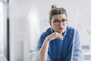 Portrait of young woman wearing glasses in office - UUF12855