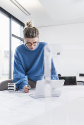 Young woman with laptop and plan working at desk in office - UUF12858