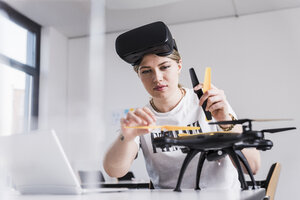 Young woman with laptop and VR glasses at desk examining drone - UUF12864