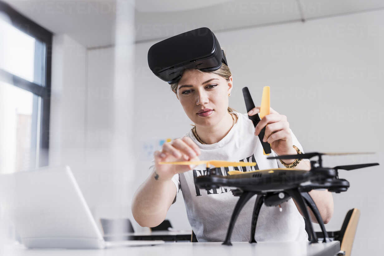 Young woman with laptop and VR glasses at desk examining drone - UUF12864 - Uwe Umstätter/Westend61