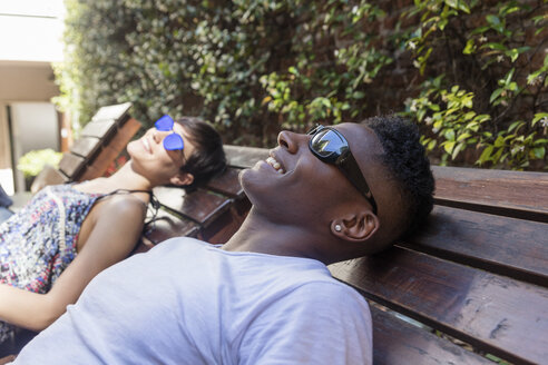 Relaxed happy couple lying on sun loungers wearing sunglasses - LFEF00059