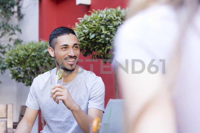 Smiling young man having a drink with friends - LFEF00065