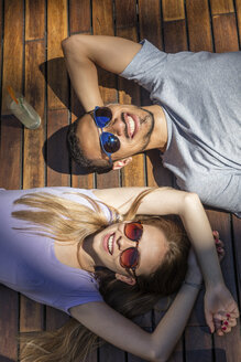 Relaxed happy couple lying on wooden terrace wearing sunglasses - LFEF00068