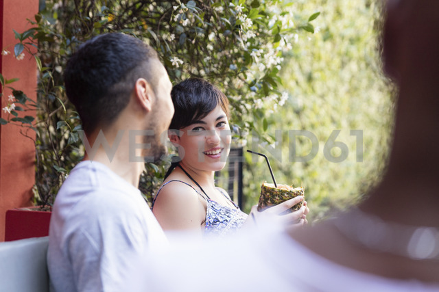 Young woman having a cocktail outside looking at man - LFEF00077