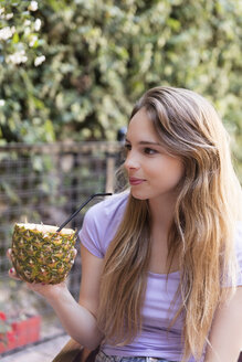 Smiling young woman drinking a cocktail in pineapple outdoors - LFEF00080