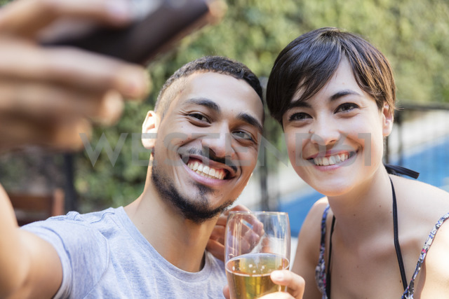 Smiling young couple having a beer and taking a selfie outdoors - LFEF00089