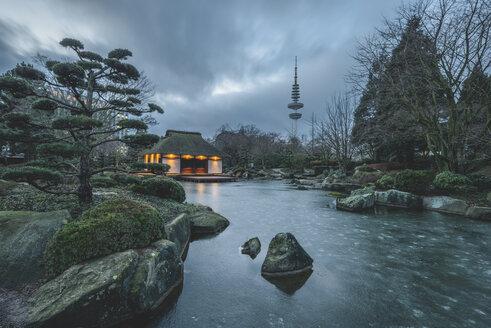 Germany, Hamburg, Japanese garden at Planten un Blomen park and Heinrich-Hertz Tower in winter - KEB00745