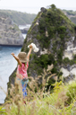 Indonesia, Bali, Nusa Penida island, girl standing on observation point - KNTF01019