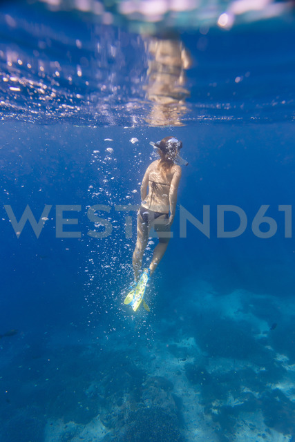 Woman with fins and snorkel diving under water - KNTF01025