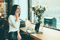 Happy young businesswoman on the phone in a coffee shop - OCAF00161