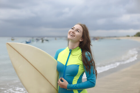 Indonesia, Bali, young woman with surf board - KNTF01038