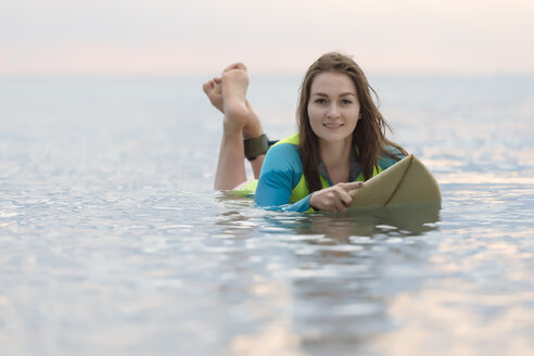 Indonesia, Bali, young woman lying on surf board - KNTF01044
