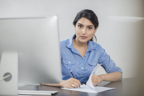 Portrait of businesswoman taking notes at desk in office - ZEF15069