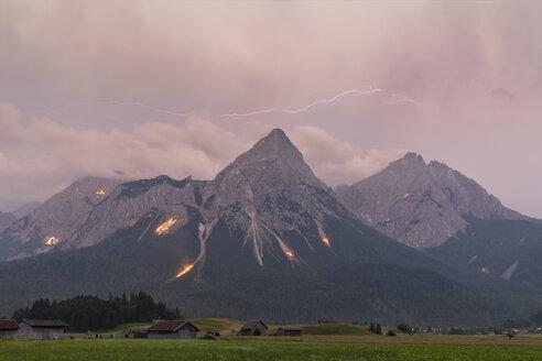 Austria, Lermoos, Ehrwalder Becken, Ehrwalder Sonnenspitze with midsummer fire, Gruenstein, Ehrwald, Mieminger Kette with thunderstorm and lightning - FOF09921