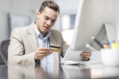 Businessman shopping online at desk in office - ZEF15080