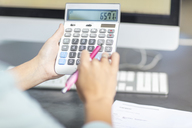 Woman at desk in office using calculator - ZEF15086