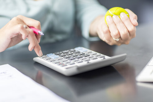 Woman at desk in office using calculator and stress ball - ZEF15089