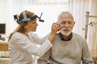 ENT physician examining ear of a senior man - ZEDF01231