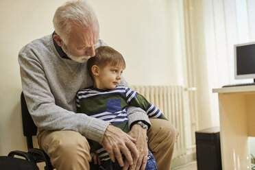 Boy sitting on grandfather's lap in waiting room - ZEDF01240