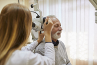 ENT physician examining ear of a senior man - ZEDF01246