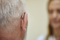 Female doctor and senior man with hearing aid - ZEDF01252