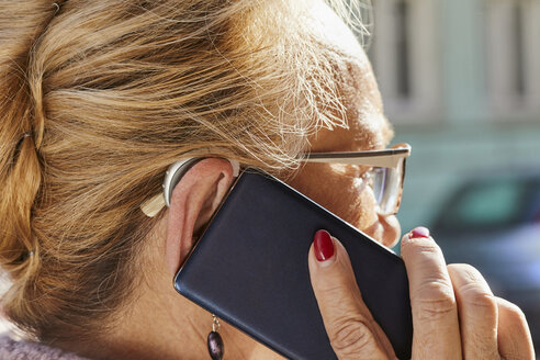 Close-up of senior woman with hearing aid using smartphone - ZEDF01255