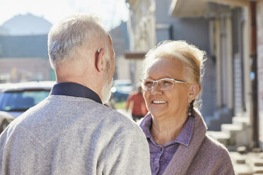 Close-up of senior man with hearing aid talking to senior woman - ZEDF01258