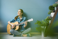 Woman relaxing in her home with potted plants, playing guitar - MOEF00864