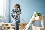 Woman refurbishing her new home with pallets, holding digital tablet - MOEF00870