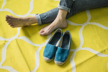 Feet and shoes of a woman, relaxing on a yellow rug - MOEF00873